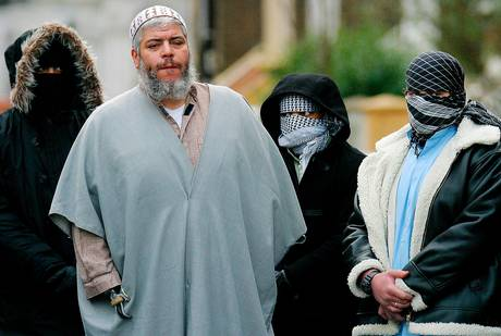Najat Hamza behind her husband, accompanied by two other upstanding British citizens.