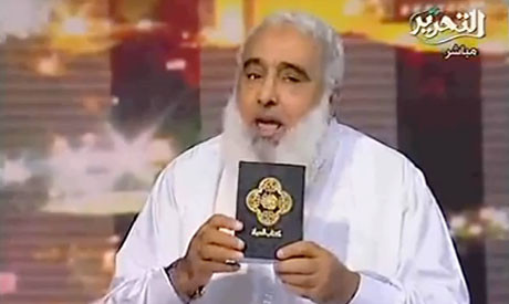 Ahmad Mahmoud Abdullah showing off his pocket-size child porn book